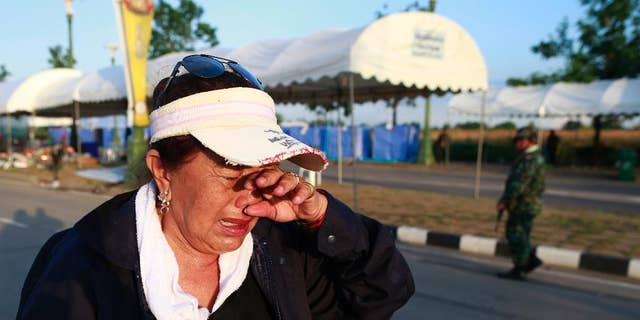 A pro-government demonstrator cries as she leaves a demonstration site after soldiers staged a coup Thursday, May 22, 2014 on the outskirts of Bangkok, Thailand. Thailand's new military junta has announced that it has suspended the country's constitution. A military statement broadcast on national television Thursday confirmed the nation's caretaker government is no longer in power but said the Senate will remain in place. (AP Photo/Wason Wanichakorn)