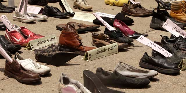 "Shoes with signs that read in Spanish: ""Where are them?"" are displayed right outside the Senate building during a demonstration to protest against violence in Mexico City, Sunday Aug. 14, 2011. The continuing tide of drug-related killings in Mexico has drawn thousands of protesters to march against violence. (AP Photo/Arnulfo Franco)"