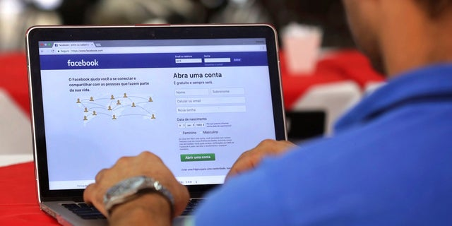 FILE - In this Thursday, Jan. 4, 2018, file photo, a man demonstrates how he enters his Facebook page as he works on his computer at a restaurant in Brasilia, Brazil. (AP Photo/Eraldo Peres, File)