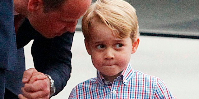 Britain's Prince William, left, holds the hand of his son Prince George.