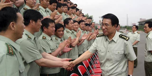 In this July 14, 2004 photo,  Xu Caihou, then member of the Secretariat of the Communist Party of China Central Committee and Director-general of General Political Department? of the People's Liberation Army, shakes hands with members of the paramilitary force in Changchun in northeast China's Jilin province.  Former No. 2 military official Xu, who was under investigation for alleged massive bribe-taking, has died in a hospital of cancer, the state Xinhua News Agency reported early Monday March 16, 2015. He was 71.(AP Photo) CHINA OUT