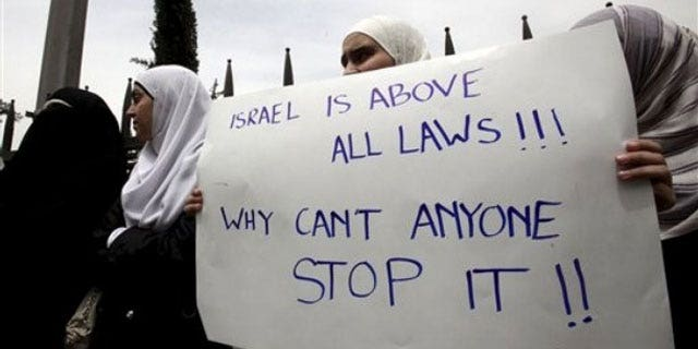 June 1: Jordanian students carry a banner during a rally in support of Turkey, in front of the University of Jordan in Amman, Jordan, after Monday's deadly commando raid by Israeli forces on ships taking humanitarian aid to the blockaded Gaza Strip. Poster reads 'Israel is above all laws, why can't anyone stop it' (AP).