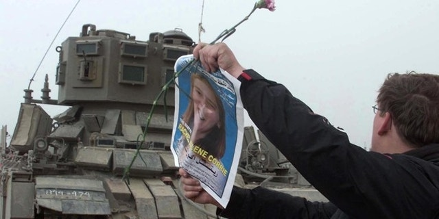 FILE: A member of the International Solidarity Movement waves a picture of pro-Palestinian activist Rachel Corrie in front of an Israeli tank during a demonstration held at the site where Corrie was killed in March 2003.
