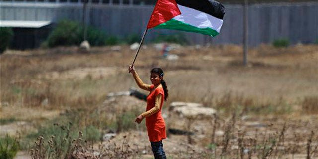 June 8: A Palestinian girl holding a national flag stands near the border line with Israel, background, during a weekly protest march against Israel, in Beit Hanoun, northern Gaza Strip.