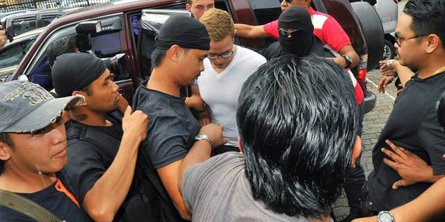 June 12, 2015: Dutch national Dylan Snel, in white shirt, center, is escorted by police as he arrives at court in Kota Kinabalu, in eastern Sabah state on Borneo island.