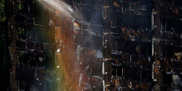 The sun creates a rainbow effect as firefighters work at the scene of a deadly blaze at a high rise apartment block in London