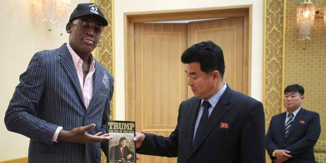 "Former NBA basketball star Dennis Rodman presents a book titled ""Trump The Art of the Deal"" to North Korea's Sports Minister Kim Il Guk"
