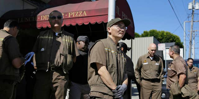 UPS workers gather outside a UPS package delivery warehouse where a shooting took place.