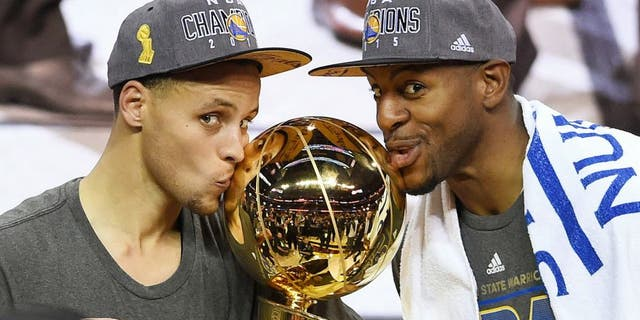 Stephen Curry #30 and Andre Iguodala #9 of the Golden State Warriors celebrate with the Larry O'Brien NBA Championship Trophy after defeating the Cleveland Cavaliers in Game Six of the 2015 NBA Finals at Quicken Loans Arena on June 16, 2015 in Cleveland, Ohio. NOTE TO USER: User expressly acknowledges and agrees that, by downloading and or using this photograph, user is consenting to the terms and conditions of Getty Images License Agreement. (Photo by Jason Miller/Getty Images)
