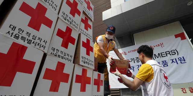 June 18, 2015: Members of South Korean Red Cross unload relief items from a truck for people who are suspected of infection and isolated at their home after having close contact with MERS patients, at Red Cross Emergency Relief Operation Center in Seoul, South Korea.