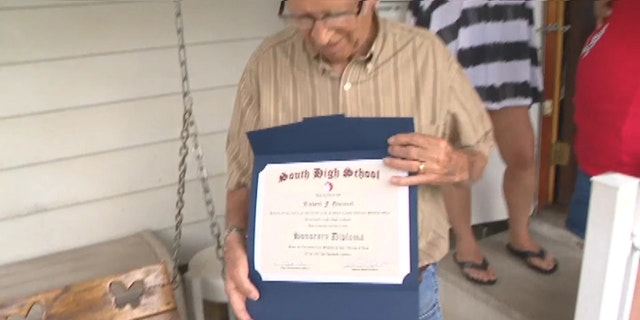 Quincel proudly holding on to his honorary high school diploma.