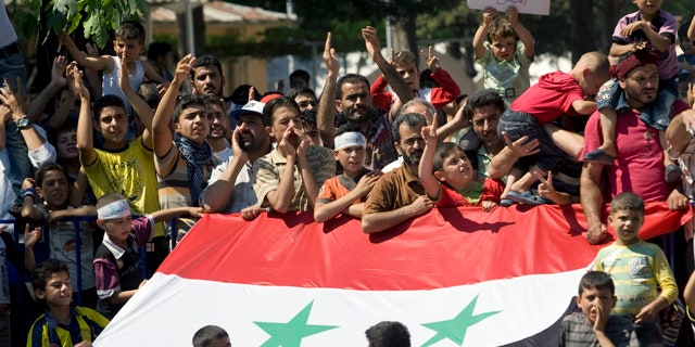 June 29: Syrian refugees demonstrate against their country's regime and its leader Bashar al-Assad in a camp in the Turkish border town of Yayladagi in Hatay province, Turkey.