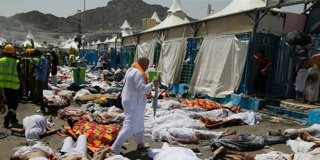 """FILE - In this Sept. 24, 2015, file photo, a Muslim pilgrim walks through the site where dead bodies are gathered after a stampede during the annual hajj pilgrimage, in Mina, Saudi Arabia. The Saudi Gazette reported the kingdom has held a workshop to review hajj security plans following a deadly crush that killed more than 2,400 pilgrims last year. The newspaper reported that the three-day workshop, which ends Thursday, March 24, 2016, reviewed emergency medical plans and """"the lessons of last year's hajj season.""""  (AP Photo, File)"""