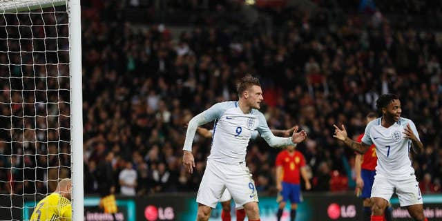 England's Jamie Vardy, center, celebrates with teammate Raheem Sterling, right, after scoring his side's second goal passing Spain's goalkeeper Jose Reina, left, during the international friendly soccer match between England and Spain at the Wembley stadium, London, Tuesday, Nov. 15, 2016. (AP Photo/Kirsty Wigglesworth)