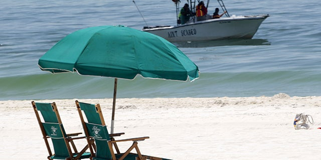 June 25: A boat skims for oil just off the beach in Pensacola Beach, Fla.
