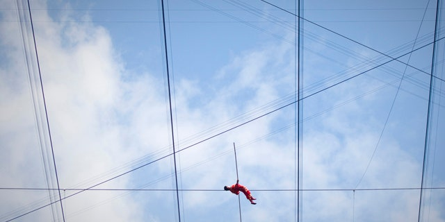 Adili Wuxor lies on a tightrope during the last day of his two-month tightrope walking performance on top of China's National Stadium, also known as the Bird's Nest, in Beijing, China, Friday, July 2, 2010. Adili, an Uighur ethnic Dawaz tightrope walking performer, has been walking the tightrope five hours a day on the top of the Bird's Nest over the past 60 days, setting a new Guinness World Record. (AP Photo/Alexander F. Yuan)