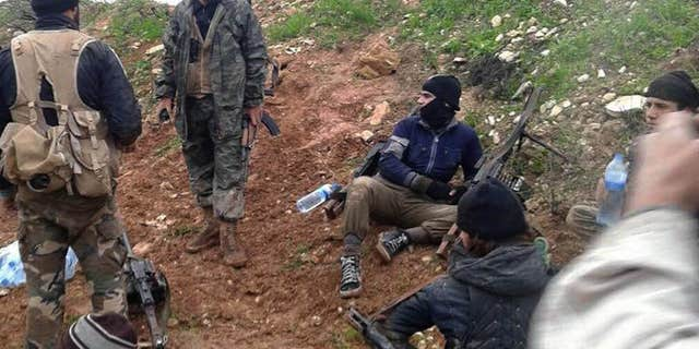 In this Dec. 14, 2014 file photo provided by the anti-government activist group Syrian Observatory for Human Rights shows fighters from the Al Qaeda-linked Nusra Front and other rebel factions resting after clashes with Syrian troops in Wadi Deif in the northwestern province of Idlib, Syria.