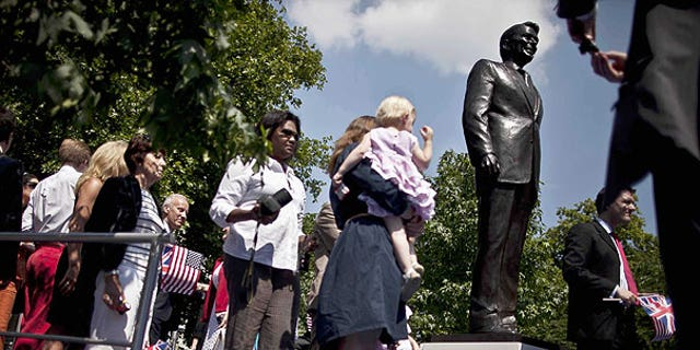 July 4: People take their turn to pose for photographs beside a statue of the late U.S. President Ronald Reagan after its unveiling outside the U.S. embassy in London.