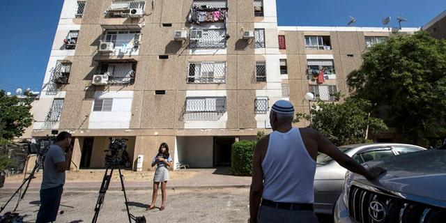July 9, 2015: Israeli journalists report outside the apartment building of Ethiopian-Israeli Avraham Mengisto, 28, in the costal city of Ashkelon, Israel.