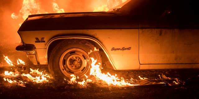 Flames from a wildfire consume a car near Oroville, Calif., on Saturday, July 8, 2017.