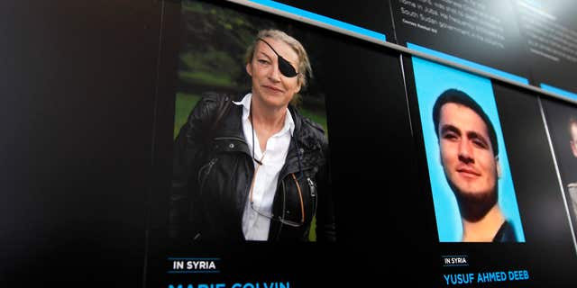 FILE- In this May 13, 2013, file photo, the photo of Journalist Marie Colvin who was killed in Syria while she was reporting from there, is seen on the wall of the Newseum during the Journalist Memorial Re-dedication ceremony of the journalists who died reporting the news in 2012 in Washington.
