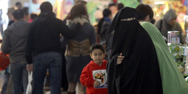 July 10: A Muslim woman wearing a burqa shops at a local market in Sydney.