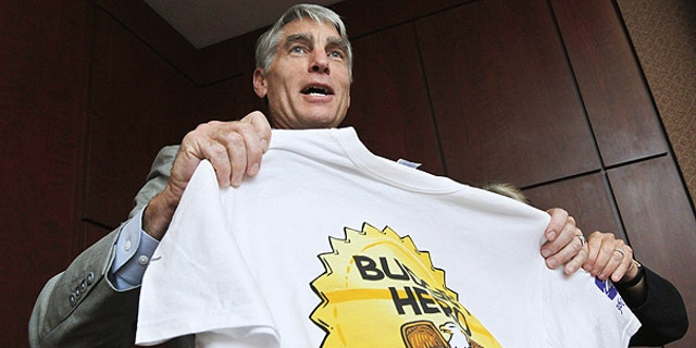 "July 13: Sen. Mark Udall, D-Colo., shows his Budget Hero shirt at the Wilson Center's re-launching of the ""Budget Game"" on Capitol Hill in Washington."