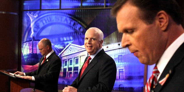 July 16: Sen. John McCain, center, looks at former congressman J.D. Hayworth, right, as political newcomer Jim Deakin checks his notes at the first Arizona Senate Republican debate in Phoenix.