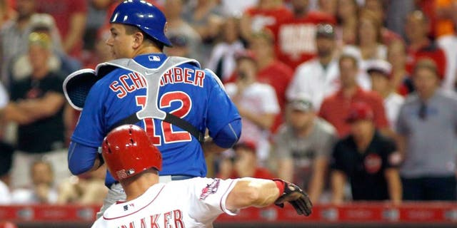 Jul 22, 2015; Cincinnati, OH, USA; Cincinnati Reds left fielder Skip Schumaker (55) is forced out a home under Chicago Cubs catcher Kyle Schwarber (12) in the eighth inning at Great American Ball Park. The Cubs won 6-5. Mandatory Credit: David Kohl-USA TODAY Sports