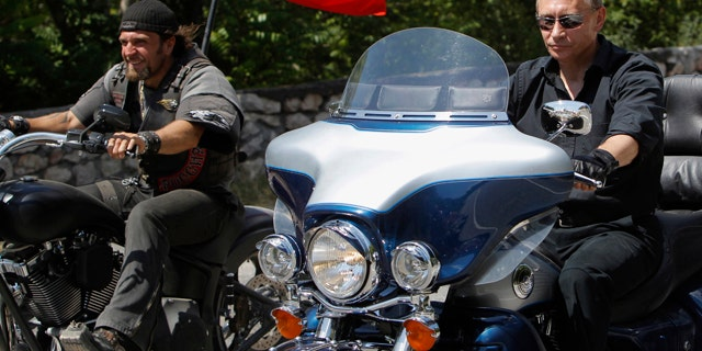 Russia's Prime Minister Vladimir Putin, right, rides Harley Davidson Lehman Trike as he arrives for the meeting with Russian and Ukrainian motorbikers at their camp near Sevastopol in Ukraine's Crimea Peninsula, Saturday, July 24, 2010. Russian flag is in the background. Putin has lept on a Harley Davidson and roared into a international biker convention in southern Ukraine. Around 5,000 bikers from Europe and beyond are gathered in Sevastopol for the annual festival on Ukraine's Crimea peninsula. (AP Photo/Sergei Karpukhin, Pool)