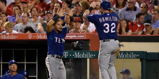 Jul 24, 2015; Anaheim, CA, USA; Texas Rangers left fielder Josh Hamilton (right) celebrates with second baseman Rougned Odor (12) after scoring during the fifth inning against the Los Angeles Angels at Angel Stadium of Anaheim. Mandatory Credit: Kelvin Kuo-USA TODAY Sports