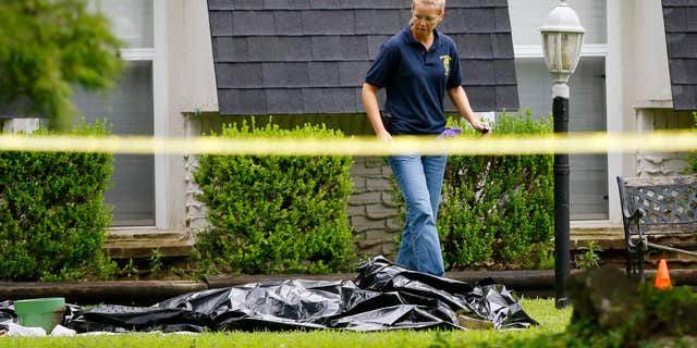 July 23, 2015: An investigator walks past a tarp covering a body in the front yard of a house in Broken Arrow, Okla.