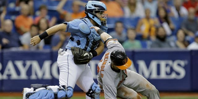 Tampa Bay Rays catcher Rene Rivera, right, tags out Baltimore Orioles' Nolan Reimold after getting caught in a rundown during the eighth inning of a baseball game Sunday, July 26, 2015, in St. Petersburg, Fla. Reimold missed the stop sign by third base coach Bobby Dickerson on a single by Jonathan Schoop off Rays pitcher Alex Colome. (AP Photo/Chris O'Meara)
