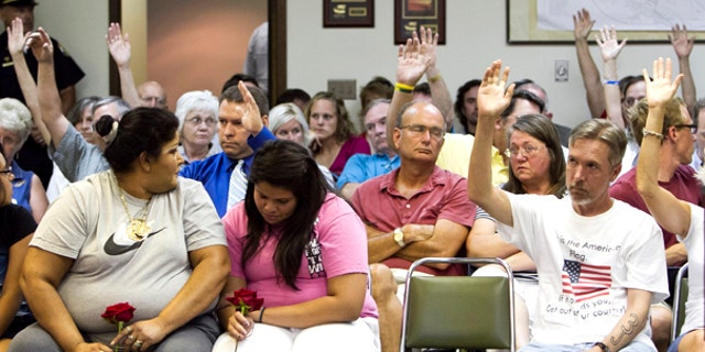 July 27: Two women in the front react to a show of hands of Fremont citizens who agree with a speaker who was in favor of implementing a city ordinance against illegal immigrants, in Fremont, Neb. (AP)
