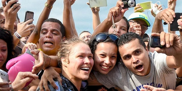 RIO DE JANEIRO, BRAZIL - JULY 29: Womens bantamweight champion Ronda Rousey of the United States takes photos with fans during open training session at Pepe Beach on July 29, 2015 in Rio de Janeiro, Brazil. (Photo by Buda Mendes/Zuffa LLC/Zuffa LLC via Getty Images)