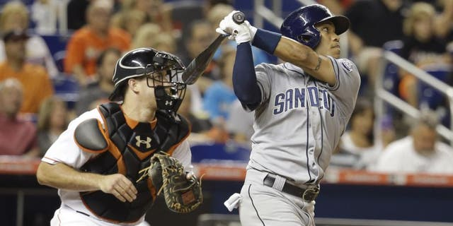 San Diego Padres' Alexi Amarista, right, follows through on a sacrifice fly to score Derek Norris in the fourth inning of a baseball game against the Miami Marlins, Friday, July 31, 2015, in Miami. At left is Miami Marlins catcher J.T. Realmuto. (AP Photo/Lynne Sladky)