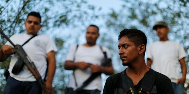 Men belonging to a self-defense group stand at a checkpoint in the town of Las Colonias, Mexico, Tuesday, Nov. 5, 2013. Two leaders of the main vigilante groups in western Michoacan state said Tuesday that they are pulling back from confronting the Knights Templar drug cartel because the Mexican government has promised to oust traffickers from the area. (AP Photo/Dario Lopez-Mills)