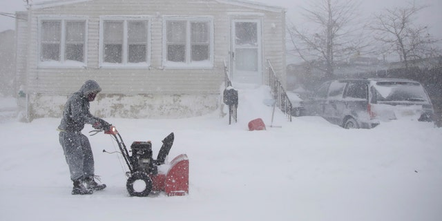 Gilberto Colin gets a head start on snowplowing his property during the middle of a snowstorm, Thursday, Jan. 4, 2018, in Neptune, N.J