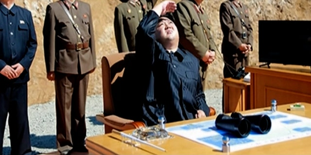North Korean leader Kim Jong Un watches the launch of an intercontinental ballistic missile.