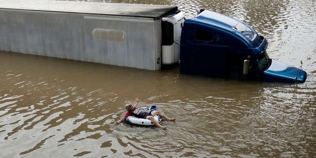 After helping the driver of the submerged truck get to safety, a man floats on the freeway flooded by Tropical Storm Harvey on Sunday, Aug. 27, 2017, near downtown Houston. (