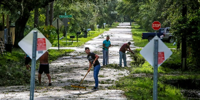 Neighbors help each other clear their road of debris in Kissimmee, Fla., Monday, Sept. 11, 2017, as residents begin to clean up after Hurricane Irma plowed through the state. (Jacob Langston/Orlando Sentinel via AP)