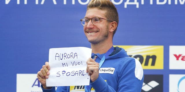 """Italy's gold medal winner Simone Ruffini shows a placard """"Aurora, you want to marry me"""" during the ceremony for the men's 25km open water swim competition at the Swimming World Championships in Kazan, Russia, Saturday, Aug. 1, 2015. (AP Photo/Sergei Grits)"""