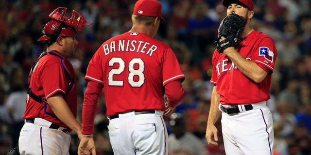 Aug 1, 2015; Arlington, TX, USA; Texas Rangers relief pitcher Sam Dyson (47) reacts after manager Jeff Banister (28) pulls him in during the eleventh inning against the San Francisco Giants at Globe Life Park in Arlington. Mandatory Credit: Kevin Jairaj-USA TODAY Sports