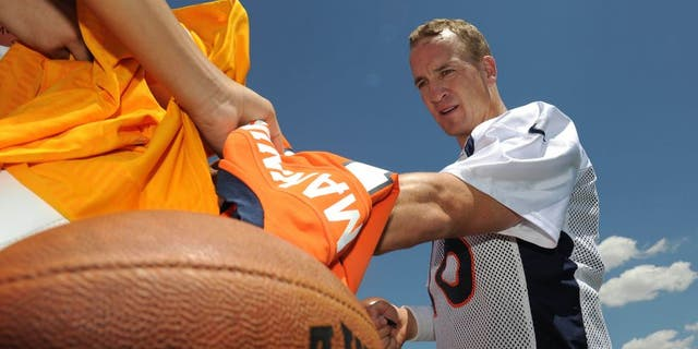 Jul 31, 2015; Englewood, CO, USA; Denver Broncos quarterback Peyton Manning (18) signs autographs following training camp activities at the UCHealth Training Center. Mandatory Credit: Ron Chenoy-USA TODAY Sports