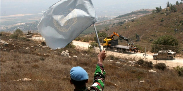 Aug. 3: A UNIFIL peacekeeper waves a U.N. flag as Israeli troops patrol the border in the southern border village of Adaisseh, Lebanon.