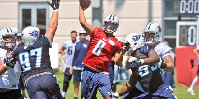 Jul 31, 2015; Nashville, TN, USA; Tennessee Titans quarterback Marcus Mariota (8) passes against Titans defensive lineman Karl Klug (97) during his first day of training camp at Saint Thomas Sports Park. Mandatory Credit: Jim Brown-USA TODAY Sports