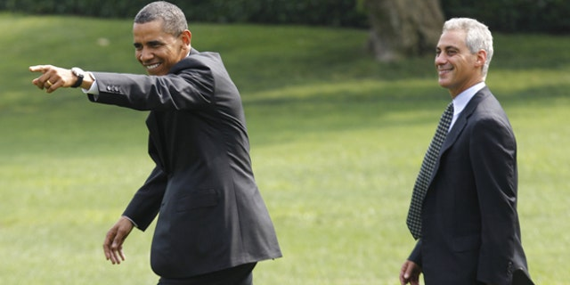 """Aug 4: President Barack Obama points to visitors singing """"Happy Birthday"""" to him as he walks with White House chief of staff Rahm Emanuel towards Marine One helicopter on the South Lawn of the White House."""