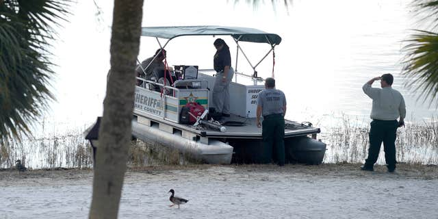 FILE- In this June 15, 2016 file photo, law enforcement officials search the Seven Seas Lagoon outside the Grand Floridian Resort & Spa in Lake Buena Vista, Fla., after Lane Graves, a two-year-old toddler, was dragged into the lake by an alligator.