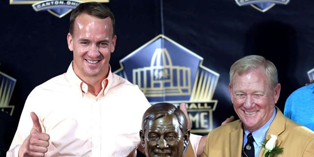 Aug 8, 2015, Canton, OH, USA; Denver Broncos quarterback Peyton Manning (left) and Bill Polian pose with the bust at the 2015 Pro Football Enshrinement Cermony at Tom Benson Hall of Fame Stadium. Mandatory Credit: Andrew Weber-USA TODAY Sports