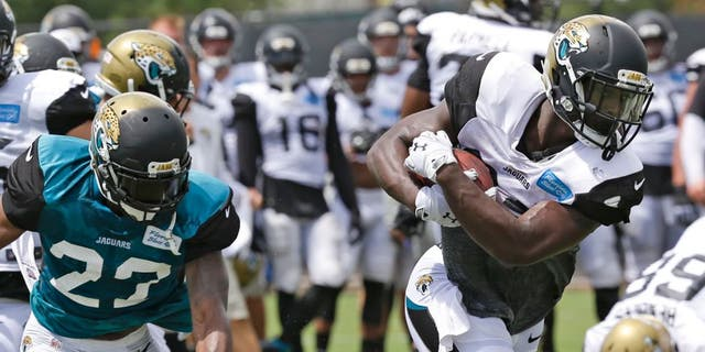 Jacksonville Jaguars running back T.J. Yeldon, front right, gets past cornerback Jeremy Harris (23) during practice at NFL football training camp, Wednesday, Aug. 5, 2015, in Jacksonville, Fla. (AP Photo/John Raoux)